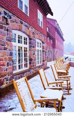 Chairs blanketed with a dusting of snow on an outdoor patio beside the historic Crater Lake Lodge which was built in 1915