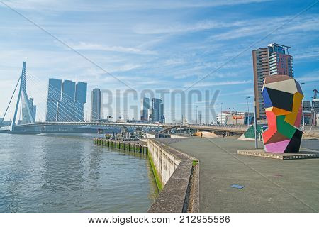 ROTTERDAM HOLLAND -AUGUST 22, 2017; Multi-colored cubic sculpture Marathon Image on waterfront in Erasmuburg district with city's stunning modern architectural buildings forming backdrop