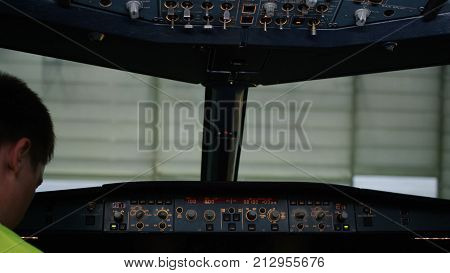 Rear View Of Pilot Operating Controls Of Corporate Jet. The Pilot Checks All The Systems. Rear View