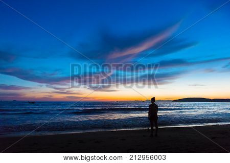 Silhouette female standing on shore at beach during sunset at Aonang Krabi Thailand