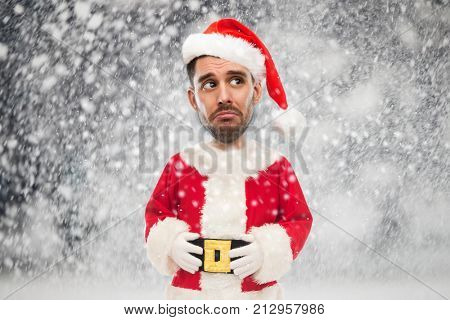 christmas, holidays and people concept - sad man in santa claus costume over snow background (funny cartoon style character with big head)