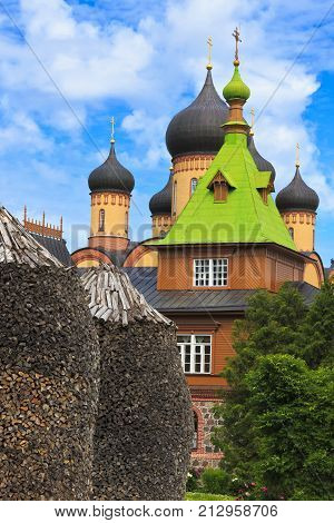 KUREMAE, IDA-VIRUMAA COUNTY, ESTONIA - July 16, 2017: Church of St Simeon and St Anna. Puhtitsa Dormition Convent. The Estonian Orthodox Church of Moscow Patriarchate. Foreground are woodpiles. poster