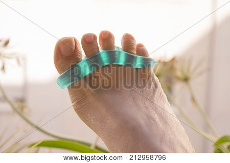 Separator for the toes. Stretching exercise. Green color