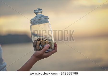 Investment, Retirement, Taxes And Passive Income Concept. Vertical View Of Coins In A Glass Jar In H