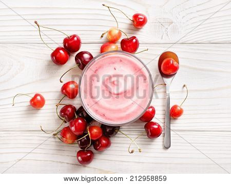 Yogurt with fresh cherry on white wooden table. Fresh yogurt. Healthy food concept. High resolution product. Top view