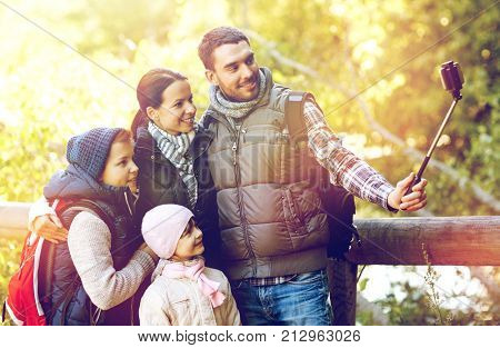 travel, tourism, hike and people concept - happy family with backpacks hiking and taking picture by smartphone on selfie stick