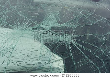 Smashed windscreen or windshield on a car wit a deployed airbag in the background