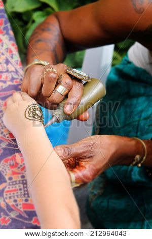 Mehndi (henna tattoo). A henna or mehendi applier at work.