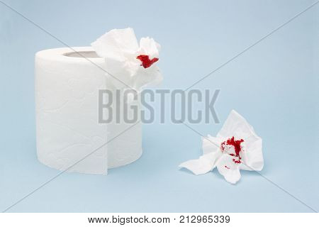 A photo of a toilet paper roll and two used bloody toilet paper sheets. Blood drops and traces. Menstrual or hemorrhoids bleeding. Hemorrhoids, constipation treatment health problems