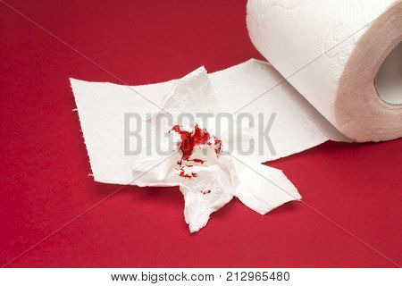 A photo of used bloody toilet paper and a toilet paper roll. Hemorrhoids, constipation treatment health problems. Menstrual or hemorrhoids bleeding. Blood drops and traces