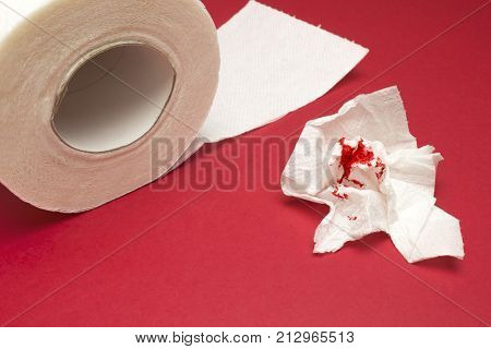 A photo of used bloody toilet paper and a toilet paper roll. Blood drops and traces. Hemorrhoids, constipation treatment health problems. Menstrual or hemorrhoids bleeding