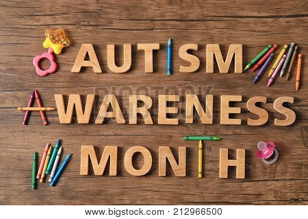Text AUTISM AWARENESS MONTH on wooden background