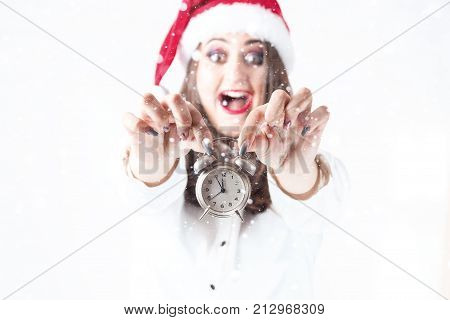 Christmas Time. Beautiful Woman Plus Size In Santa Claus Hat Holding Alarm Clock. New Year Concept.