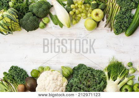Green vegetables and fruits on the white wooden table, copy space for text in the middle, horizontal, top view, selective focus