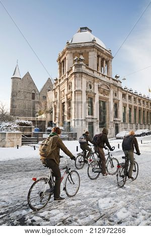 GHENT BELGIUM - CIRCA 2010: School children cycling in winter through the streets of Ghent Belgium