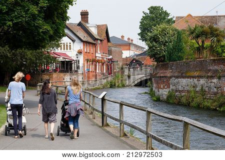 WINCHESTER UK - CIRCA 2012: Women with pushchairs walk beside the River Itchen in Winchester Hampshire UK