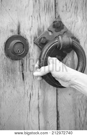 Hand knocking on a wooden door outside.