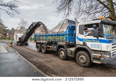 LONDON UK - CIRCA 2013: Highway contractors resurface the tarmac of a suburban road in London UK