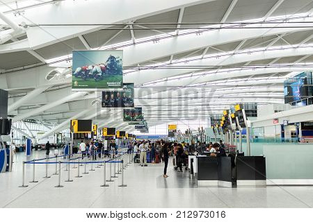 LONDON UK - CIRCA 2017: Passengers queue for check in at the departure hall in Terminal 5 Heathrow Airport