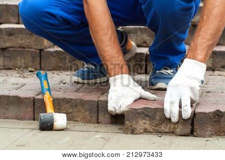 Laying Paving Slabs by mosaic close-up. Repairing sidewalk. Workers laying stone paving slab. laying of paving slabs by a professional master builder in blue overalls