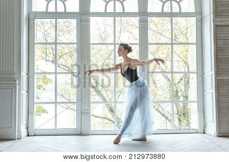 Ballerina in a blue ballet skirt. Beautiful graceful ballerine practice ballet positions in tutu skirt near large window in white light hall. Young classical Ballet dancer side view. Ballet class training, high-key soft toning.