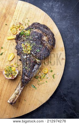 Australian barbecue dry aged wagyu tomahawk steak with fruit relish as close-up on old wooden board