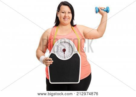 Joyful overweight woman with a weight scale and a small dumbbell isolated on white background