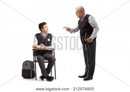 Teacher scolding a teenage student seated in a school chair isolated on white background