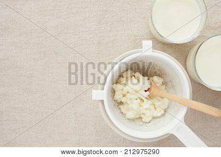 Organic probiotic milk kefir grains Tibetan mushrooms in plastic sieve and kefir milk in glass containers poster