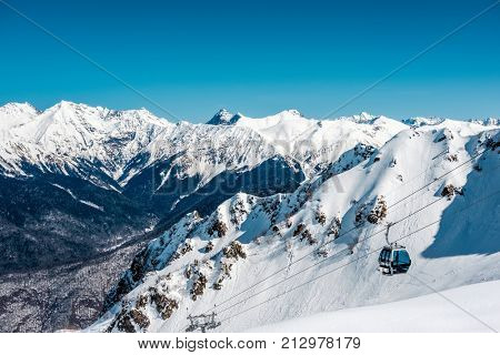 Winter mountain landscape. Caucasus ridge covered with snow in sunny day. Krasnaya Polyana, Sochi, Russia