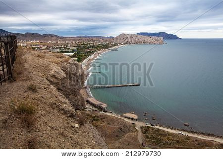 Crimea, Sudak - October 16, 2017: Tourists visits Towers and walls of The Genoese Fortress in Sudak, Museum-reserve Sudak fortress , Crimea. View from the fortress on a beach