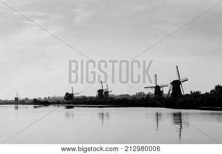 Line of silhouette windmills along Kinderdijk canal a popular tourist destination with it's scenic fields ponds canls and windmills.