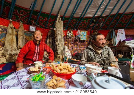 BAYAN-OLGII, MONGOLIA - SEP 28, 2017: Kazakhs family of hunters with hunting golden eagles inside their the mongolian Yurts. In Bayan-Olgii Province is populated to 88,7% by Kazakhs.