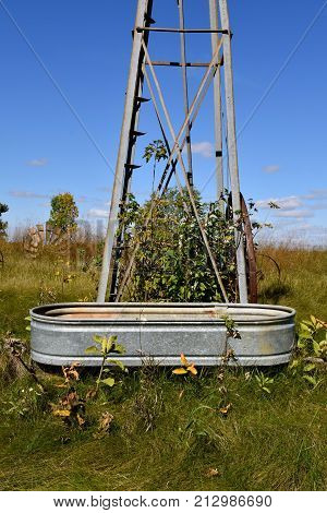 An old galvanized water (stock) tank in front of a wind mill