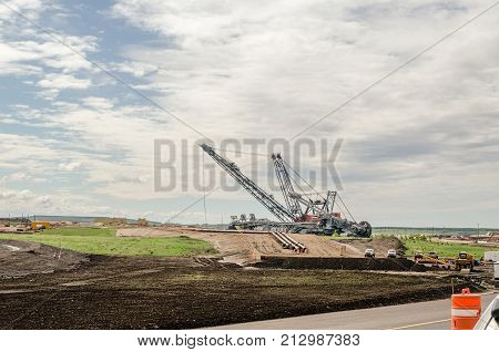 Heavy equipment for oil sands industry red crane and huge digger digging the ground for the pipes