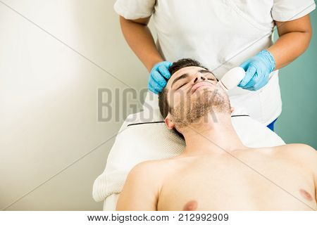 Man Getting A Facial Exfoliation
