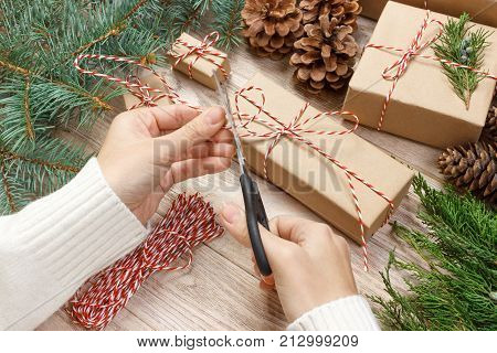 Christmas gift wrapping background. Female hands packaging christmas present wrapped in kraft paper top view. Winter holidays concept flat lay. Woman holding Christmas gift box.