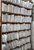 A cupboard full of paper files / inefficiency of paper based filing system poster