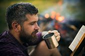 Man traveler read and drink at campfire flame. Sustainable education environment concept. Camping hiking lifestyle. Summer vacation activity. Hipster hiker with book and mug at bonfire on nature. poster