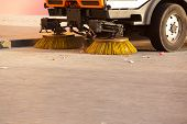 Yellow urban sweeper cleans road from dirt with a round brush poster