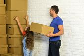 Girl and man with busy faces on white brick wall background. Daughter puts hands up and father puts boxes in pile. Accommodation moving and family concept. Kid and guy move into new home or move out poster