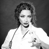Closeup view portrait of one serious sexual beautiful brunette medical worker with stethoscope in white nurse uniform holding injecting suringe for botox shot or drugs in studio square picture poster