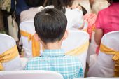 Close up behind of small guest. Boy sitting in meeting room on ceremony day poster