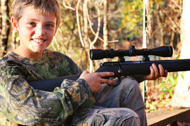 little boy hunting with a gun smile