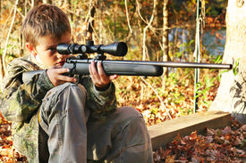 little boy hunting with a gun