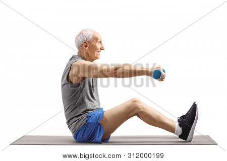 Full length profile shot of a senior man exercising with dumbbells and sitting on an exercise mat isolated on white background