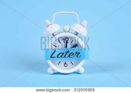Procrastination, Delay And Urgency Concept. White Alarm Clock With A Sticky Note With Text Later.