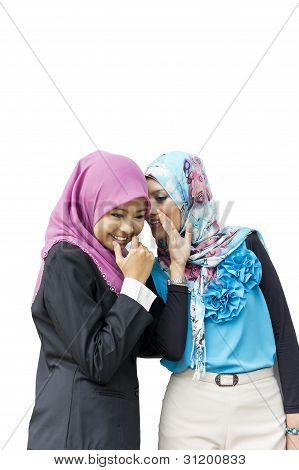 Two young Muslim woman gossiping isolated on white backgroud