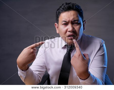 Asian Mbusinessman Pointing Himself With Unhappy Displeased Expression As If He Confused To Be Accus