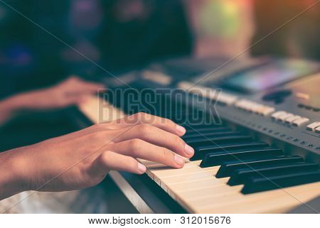 Playing The Piano Keyboard Close Up ,cropped Hands Of Kid Playing Piano In The Classroom. An Image O
